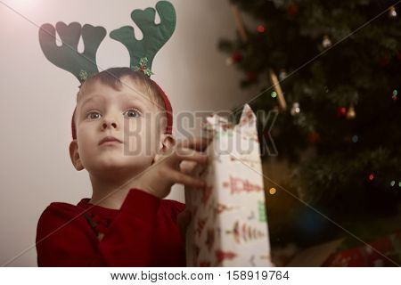 Boy waiting for his parents to let him open his presents