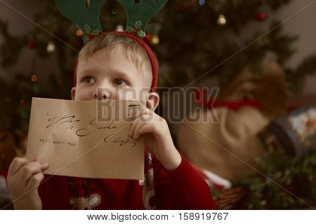 Boy showing his letter so Santa