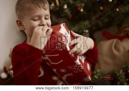 Boy being happy while opening a gift