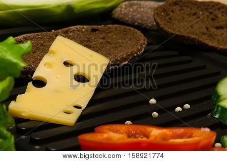 piece of cheese fell from the bread on a grill