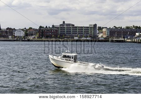 Portland Maine USA - August 9 2009: Water taxi hurrying along waterfront in Portland Maine