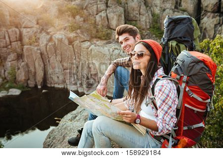 Traveler couple with map near the canyon. sittong on slope
