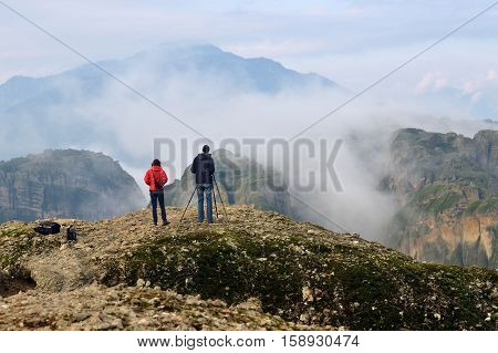 Two unidentified photographers a man and woman taking a pictures of the Meteora mountains at sunrise. Greece