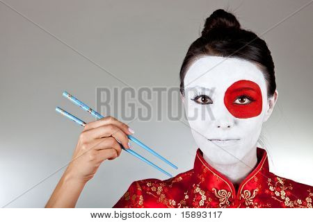 Japanese woman with chopsticks and the flag painted on her face