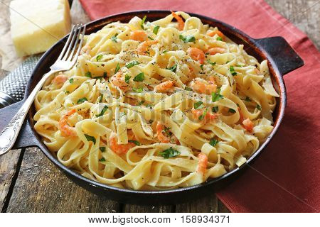 Pan with tasty alfredo pasta, red napkin, grater, cheese and fork  on wooden table