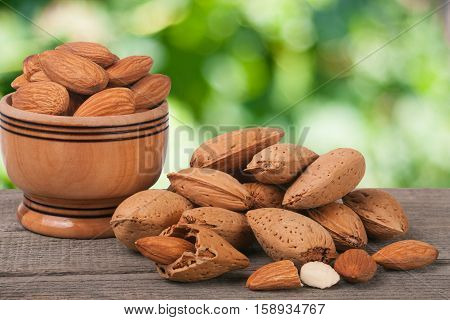 almonds in a bowl on the old wooden board with blurred garden background.