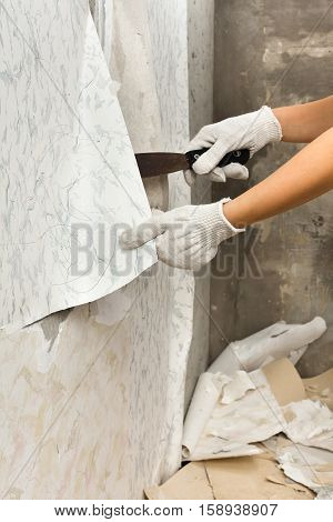 hands in gloves removing old wallpapers with spatula during repair