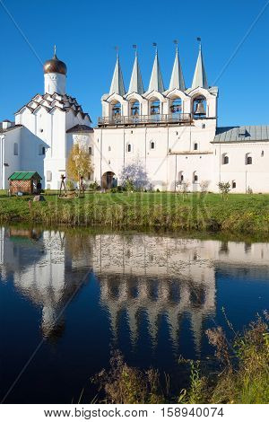 The old bell tower of the Tikhvin assumption monastery and its reflection in the monastery pond, October evening. Tikhvin, Russia