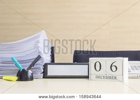 Closeup white wooden calendar with black 6 december word on blurred brown wood desk and wood wall textured background in office room view with copy space selective focus at the calendar