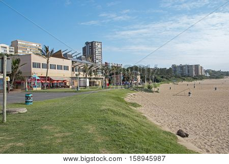AMANZIMTOTI DURBAN SOUTH AFRICA - NOVEMBER 27 2016: Quiet early morning grass verge and empty beach against commercial and residential buildings and blue sky on beach front in Amanzimtoti
