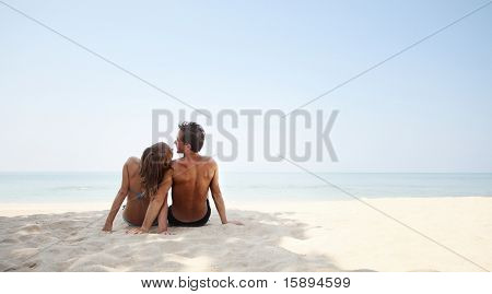 Young lovers sitting on warm sand at sunny day