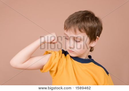 Young Boy Showing Off His Muscles