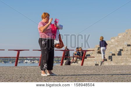 DNEPR, UKRAINE - OCTOBER 02, 2016:Mature woman talking on cellular using speaker standing on a Dnepr river embankment in center of the Dnepr city at warm and sunny autumnal weekend October 02, 2016
