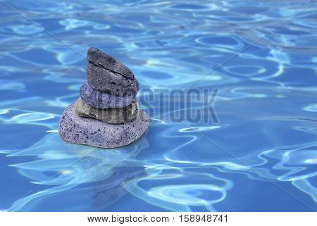 View of four pebbles balancing on each other on a              watery background