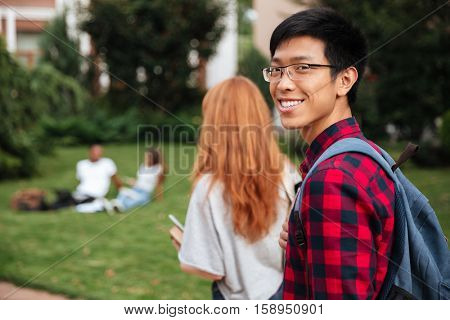 Happy asian young man student with backpack walking outdoors