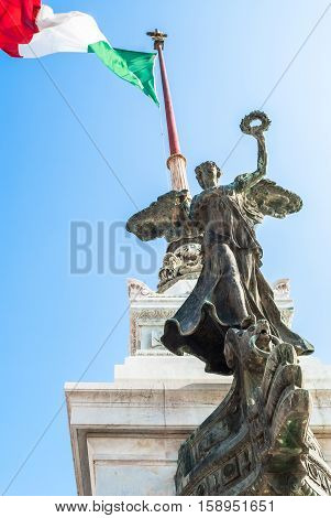 View of Italian national flag in front of Altare della Patria (Altar of the Fatherland) the equestrian sculpture of Victor Emmanuel and statue of the goddess Victoria riding on quadrigas on top