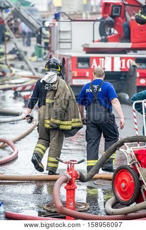 fire fighter and rescuer walking away building in the drops of water after putting out the fire