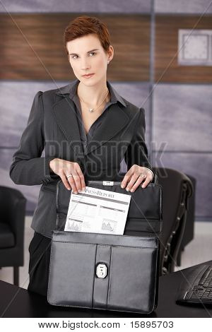 Serious businesswoman taking out document from briefcase, standing at desk in office, looking at camera.?