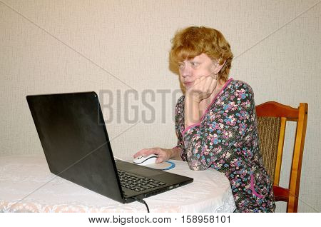 Woman sitting at a computer and watching the latest news via the Internet.