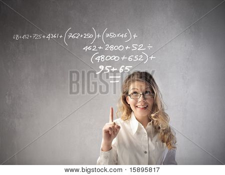 Beautiful businesswoman indicating a calculation on a blackboard