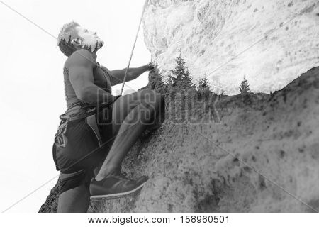Young fearless man climbing a steep wall in mountain