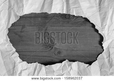 Creased White Paper Torn Hole Located On Empty Brown Wooden Board With Copyspace. Grey And White Colors.