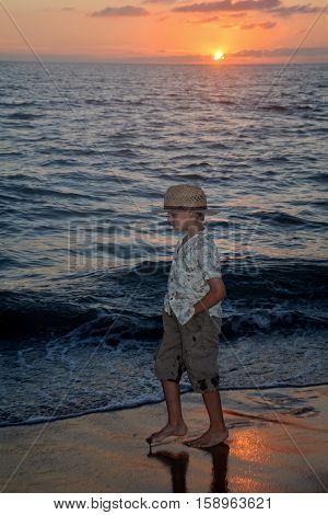 Small boy runs at the sundown along the beach