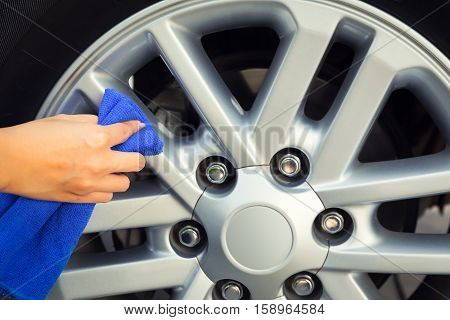 Asian woman's hand wiping surface of wheel by micro fiber cloth.