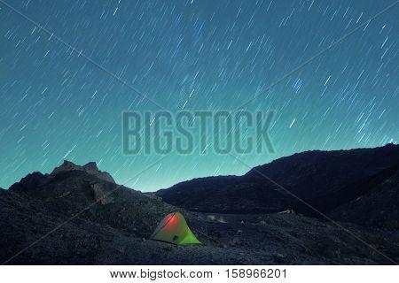 stars trails on lighting tent in Etna Park lunar landscape, Sicily