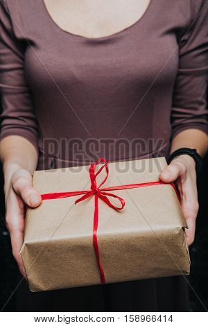 Close up crop hands holding wrapped present with red ribbon isolated on black.