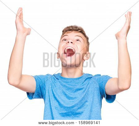 Happy cute child reaching out his palms and catching something. Half-length emotional portrait of caucasian teen boy wearing blue t-shirt, surprised. Funny teenager trying to catch something, isolated on white background.