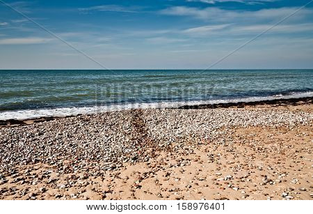 landscape with views of the Baltic Sea, on the banks of large and small stones and sand, wet stripe up water, small waves and endless horizon, blue sky and bright water, preset, processed, deep dark
