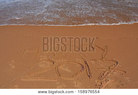 Happy 2017 written on sand at sunset. Happy 2017 lettering on the beach.