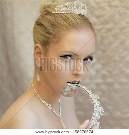 Attractive hot blond woman eating crown. Jewelry, liquid silver