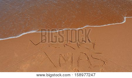 Merry Xmas written on sand at sunset. Merry Christmas lettering on the beach.