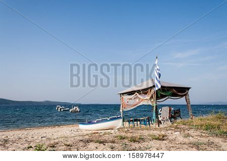 Boats on the calm beach in sunny day in Greece. Athos, Chalkidiki, Northern Greece