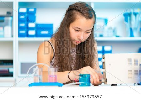Student teen girl with experiment PEM proton exchange membrane reversible fuel-cell