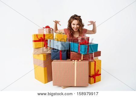 Young beautiful curly girl among gift boxes Isolated Copy space