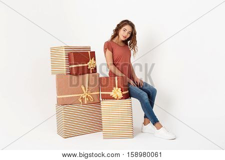 Young beautiful girl sitting on big gift box Isolated Copy space