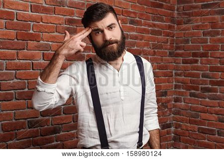 Young handsome man in suit with suspenders posing pointing fingers at head over brick background. Copy space.