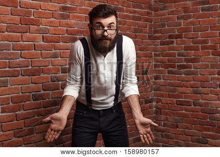 Young handsome man in suit with suspenders and glasses gesturing over brick background. Copy space.