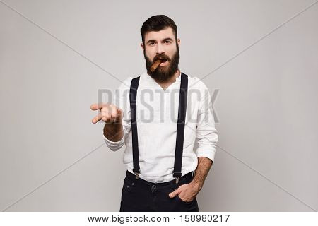 Young handsome man in suit with suspenders posing over white background. Copy space.