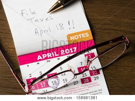 Gold Pen Laying On Calendar For Tax Day