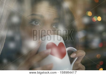 Girl enjoying a hot drink while it is snowing outside