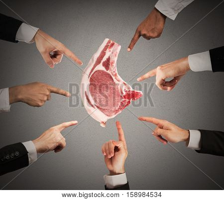 Man holding a slice of raw beef while hands pointing accusing