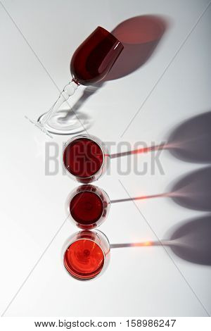 red wine glasses with shadows view from top om white background