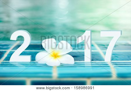 Happy new year card 2017. Number 2017 text with white Plumeria flower on ceramic tile border of swimming pool over bokeh blur water background.