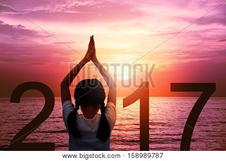Happy new year card 2017. Silhouette of girl doing Yoga vrikshasana tree pose on tropical beach with fantastic sunset sky background. Kid standing as part of the Number 2017 sign and watching sunrise.