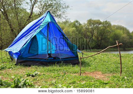 Blue deployed tent stands on river bank in green forest on summer day