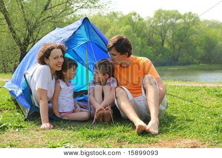 Happy family - mother, father, little girl and boy - sitting in blue tent on green lawn on bank of river at sunny day